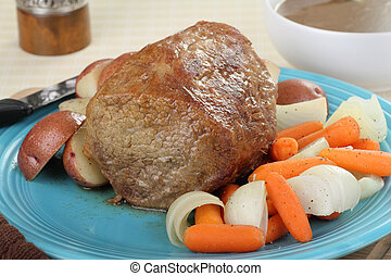 Pot Roast Meal - Whole pot roast with vegetables on a...