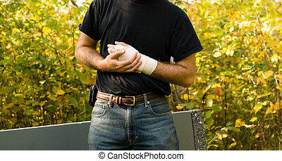 Sprained Wrist - A man holding his wrist with a tensor...