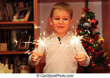 Cheerful boy watching sparklers - Cheerful little boy...