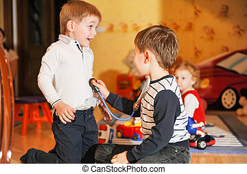 Children play doctor - Merry children playing as doctor and...