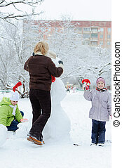 Mother and children building snowman
