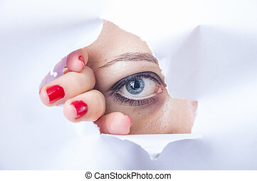 Woman looking through paper hole - An image of wman looking...