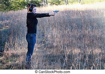 Woman Shooting a Firearm - Mother teaching her young...