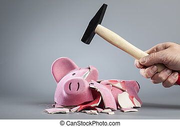 Robbing piggy bank with hammer - Hand holding hammer over a...