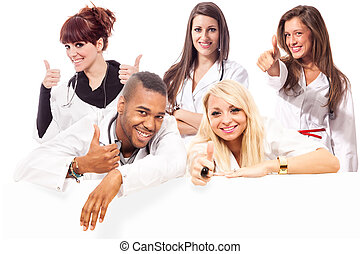 Young medical students smiling making positive thumb gesture...