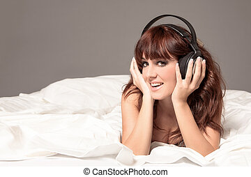 Smiling woman in lingerie and headphones on the bed -...