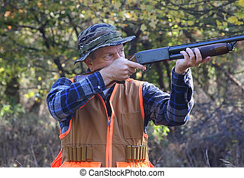 Hunter In Fall - Hunter shooting a shotgun in a field in...