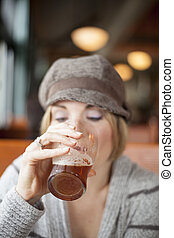 Young Woman Drinking Inda Pale Ale - Young woman in cute...