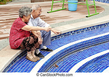 an intimate senior couple sitting beside a pool