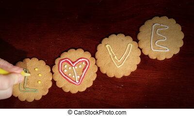 Drawing on ginger cookies The word love