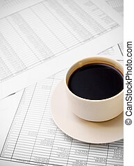 Cup of coffee on documents.