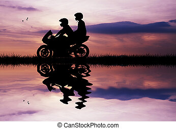 couple on a motorcycle at sunset