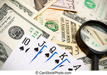 Game cards and magnifier on dollars