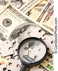 Magnifier and puzzle on dollars.