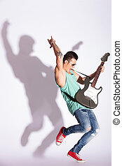 man practicing rock on electric guitar - full length photo...