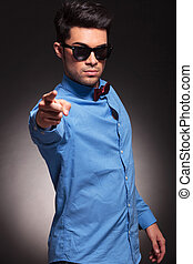 fashion man in sunglasses pointing to the camera