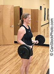 Barbell curl - Woman working out with a barbell at a gym....