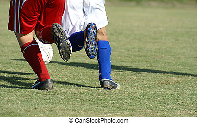 Two soccer players chasing the ball. - Two soccer players...
