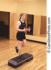 Blonde woman working out in the gym with hand weights -...