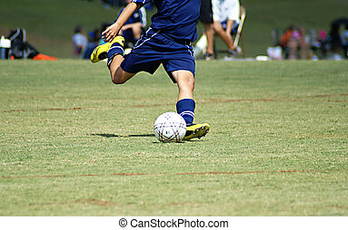 Boy striking at a soccer ball in a game. - Young boy strking...