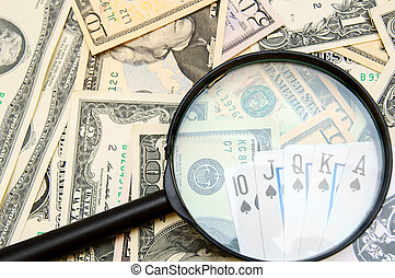 Magnifier and game cards on banknotes
