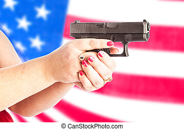 gun with flag - Woman's hands holding a small handgun with...