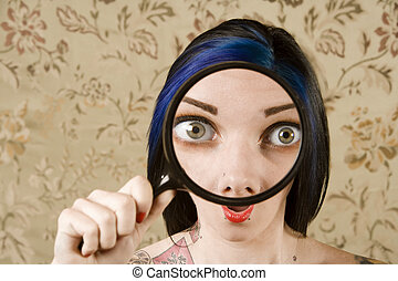 Pretty Woman with a Magnifying Glass in front of her Face -...
