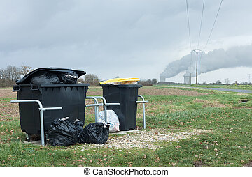 Pollution - Household waste container in front of nuclear...