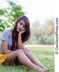 Depressed young woman sitting alone in garden