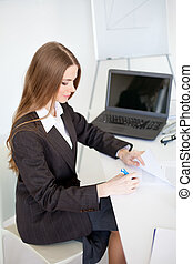 Portrait of a beautiful young business woman doing some...