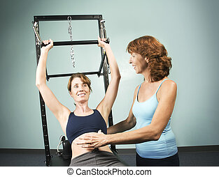 Pilates with a Trainer - Athletic woman working out with a...
