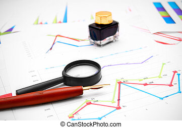 Pen, ink and a magnifier on graphs.
