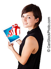 Young woman looking at modern tablet with present boxes -...
