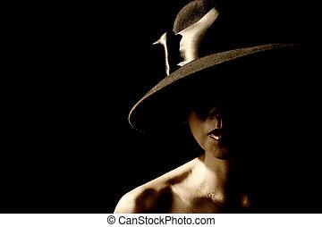 Woman in shadow wearing a black hat