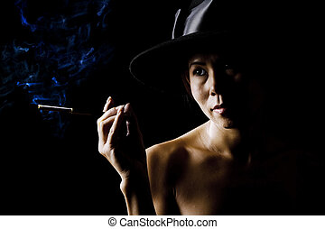 Woman in shadow wearing a black hat with cigarette