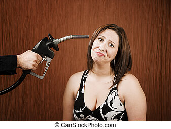 Woman with Gas Nozzle to her Head