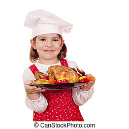 little girl cook holding roasted chicken