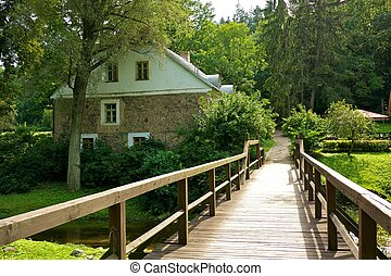 Wooden bridge and an old stone house.