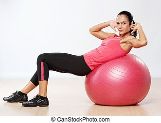Beautiful athlete woman with a fitness ball