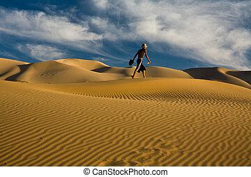 Man walking alone across desert dunes - A man walks across...
