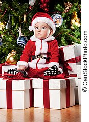 Little Santa boy sitting on a  gift boxes.
