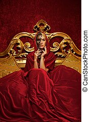 Beautiful woman with a carnival mask sitting in bed