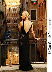 Beautifiul woman in black dress on a bridge