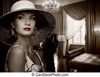 Beautiful woman in hat in luxury room.