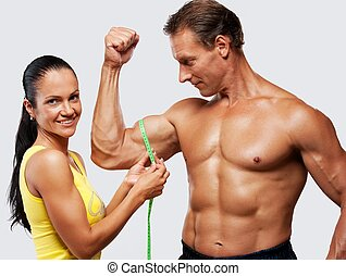 Woman measuring athletics man biceps