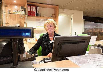 Senior volunteer female cashier at museum - Senior volunteer...