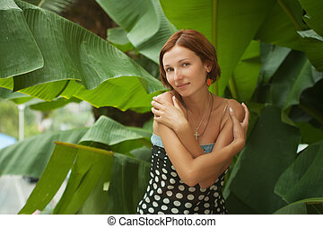 Beautiful woman on leaves of palm background