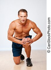 Handsome muscular man doing fitness exercise.
