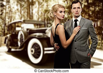 Retro couple against old car
