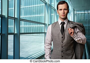 Man in grey suite in modern building.